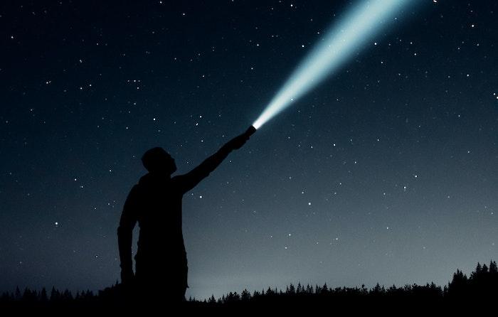 shining flashlight into the night sky
