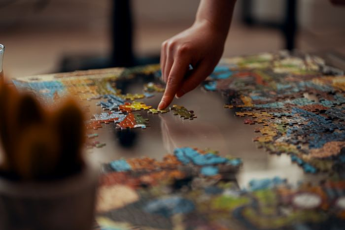 a hand putting puzzles together
