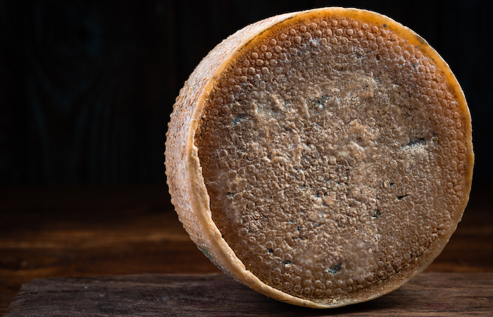 whole cheese wheel on a wooden board